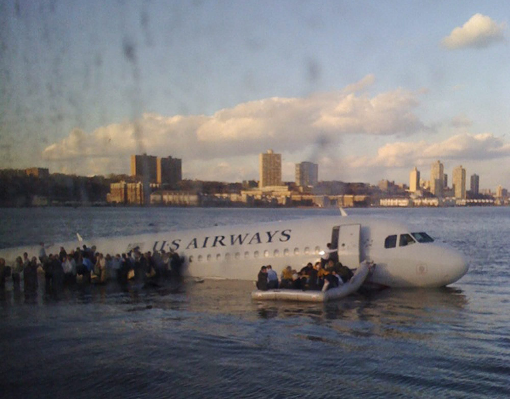 In this photo taken by a passenger on a ferry, airline passengers egress a US Airways Airbus 320 jetliner that safely ditched in the frigid waters of the Hudson River in New York, Thursday Jan. 15, 2009 after a flock of birds knocked out both its engines. All 155 people on board survived. (AP Photo/Janis Krums)