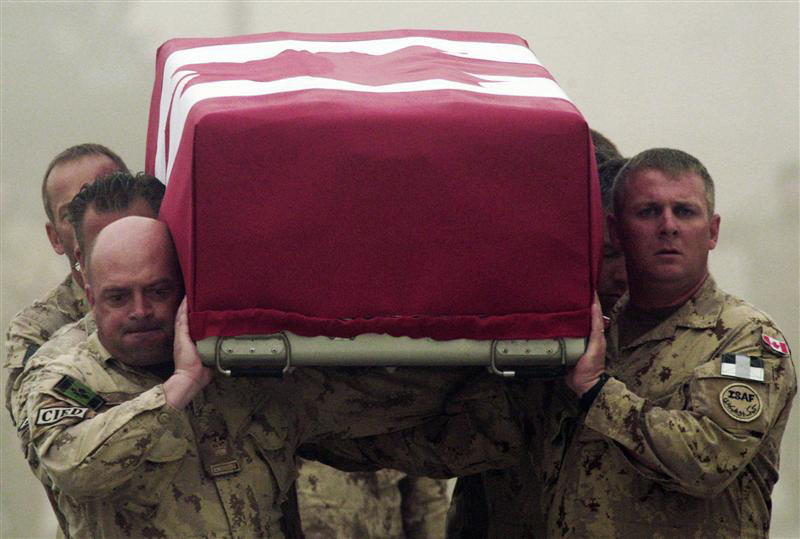 Canadian Army soldiers carry fallen comrade
