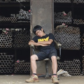 A vendor naps on a chair in front of shelves of steel commodities at a metal products market in Hefei