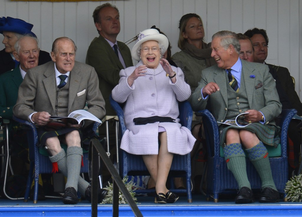 Members of Britain's royal family cheer as competitors participate in a sack race at the Braemar Gathering in Braemar