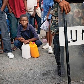 Haitians queue for aid by a UN peacekeep