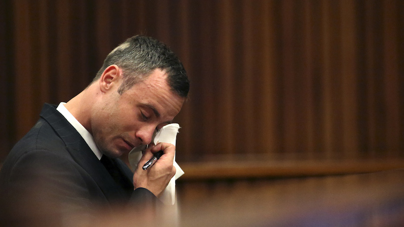 Olympic and Paralympic track star Oscar Pistorius reacts as he sits in the dock during his trial for the murder of his girlfriend Reeva Steenkamp, in Pretoria