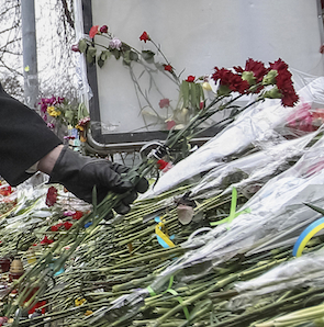 Canada's Foreign Minister John Baird lays flowers at a make-shift memorial for those killed in recent violence in Kiev