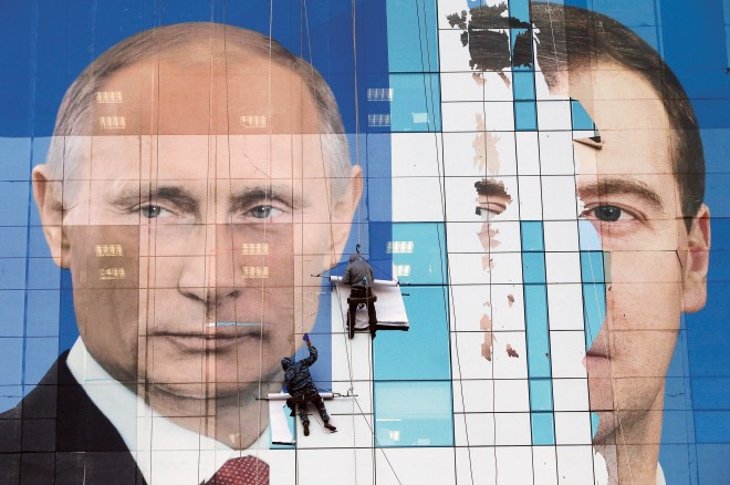 Workers attach a pre-election poster featuring Russia's President Dmitry Medvedev (right) and Prime Minister Vladimir Putin. (Eduard Korniyenko/Reuters)