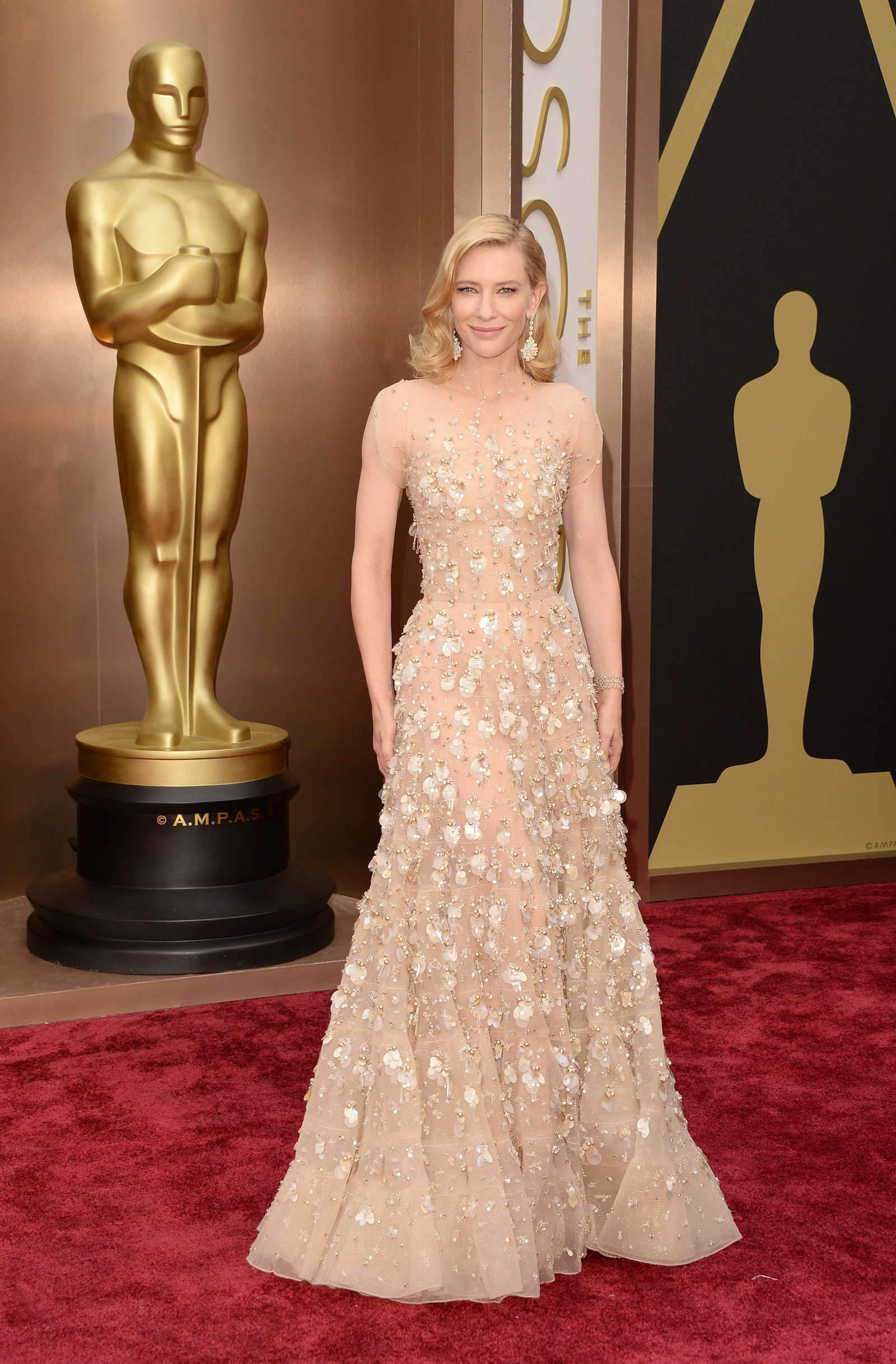 Best Actress Oscar winner Cate Blanchett is statuesque in a soft gold sequined Armani Prive glowing with gold Swarovski crystals.