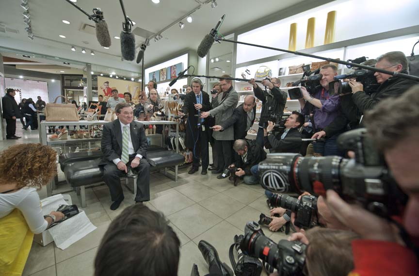 Canadian Finance Minister Jim Flaherty speaks to the press as he tries on new shoes as he shops in Ottawa on March 28, 2012. (Rogerio Barbosa/AFP/Getty)