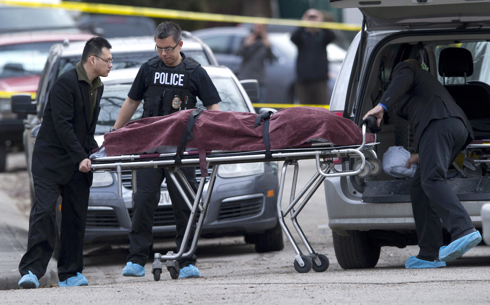 Police remove a body from the scene of a multiple fatal stabbing in northwest Calgary, Alberta on Tuesday, April 15, 2014. Police say five people are dead after a stabbing at a house party. THE CANADIAN PRESS/Larry MacDougal