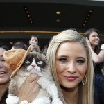 Grumpy Cat gets her photo taken with a fan as she arrives at the 2014 MTV Movie Awards in Los Angeles