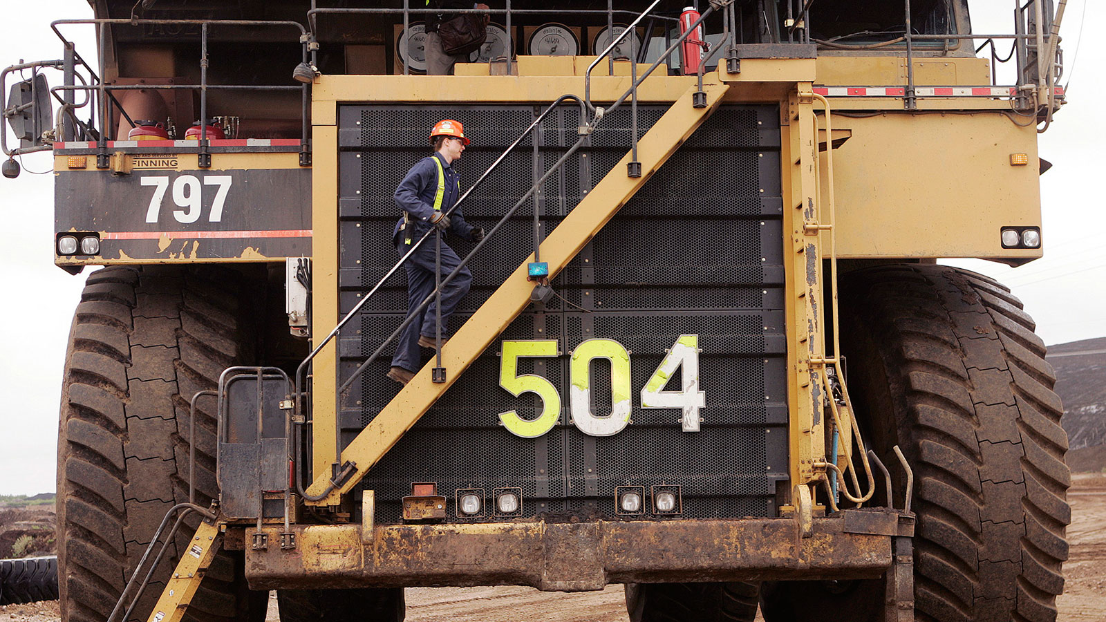 Michelle Noer climbs the steps to the world's largest dump truck at the Syncrude Aurora mine near Fort McMurray, Alta. (Todd Korol/Reuters)