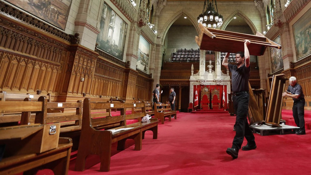 A worker carries a bench while preparing the Senate chamber on Parliament Hill in Ottawa