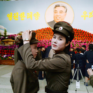 North Korean female soldiers prepare to take a commemorative photograph in front of a flower exhibition featuring North Korea's late founder Kim Il Sung in Pyongyang