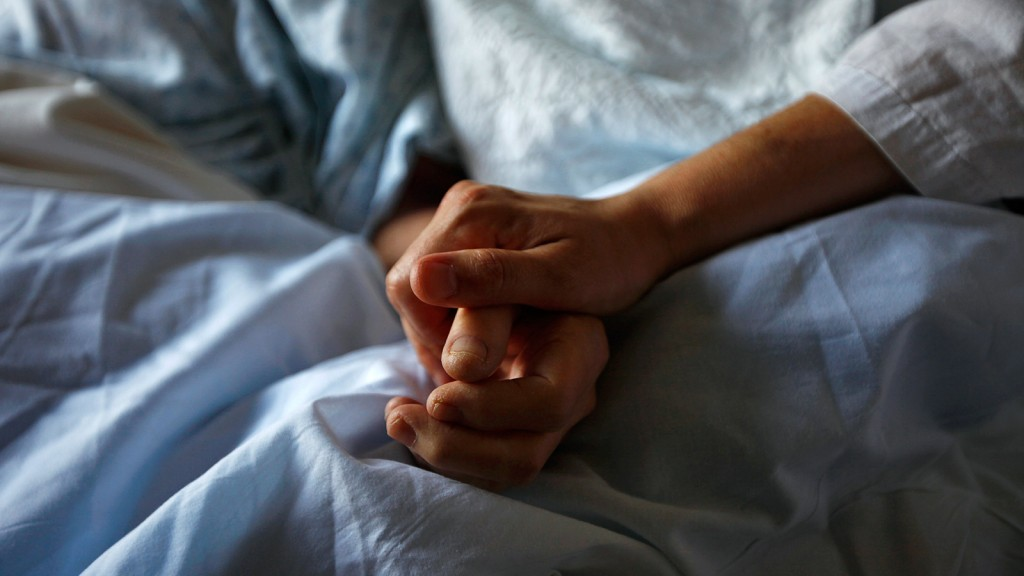 A woman holds the hand of her mother who is dying from cancer during her final hours at a palliative care hospital in Winnipeg July 24, 2010. Picture taken July 24, 2010. (Shaun Best / Reuters)