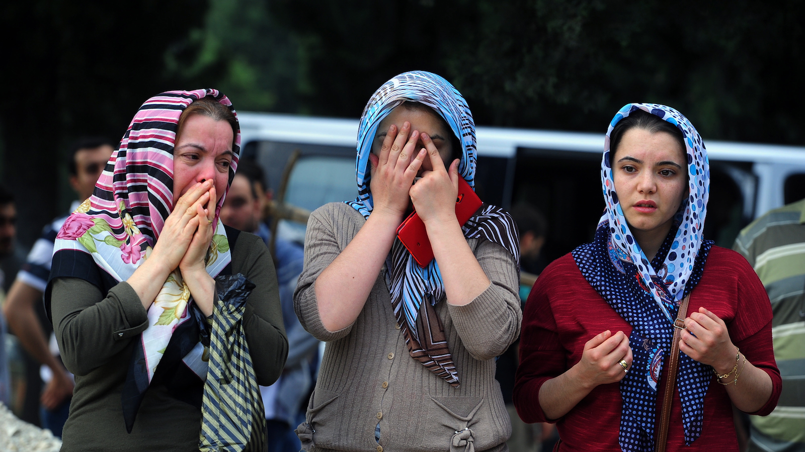 People attend a mine accident victim's burial in Soma, Turkey, Wednesday, May 14, 2014. Nearly 450 miners were rescued, the mining company said, but the fate of an unknown number of others remained unclear as bodies are still being brought to the surface and burials are underway after one of the world's deadliest mining disasters. (AP Photo/Emre Tazegul)