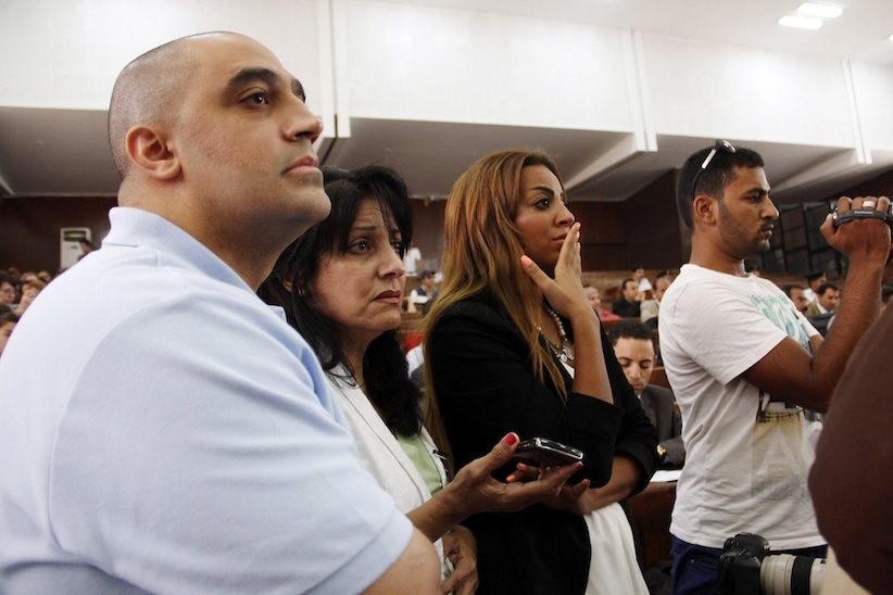 Adel Fahmy, brother of Mohamed Fahmy, left, Wafa Bassiouni, mother of Mohamed Fahmy, second left, and his fiance, third left, watch proceedings in a courtroom in Cairo, on Monday. (AP Photo)