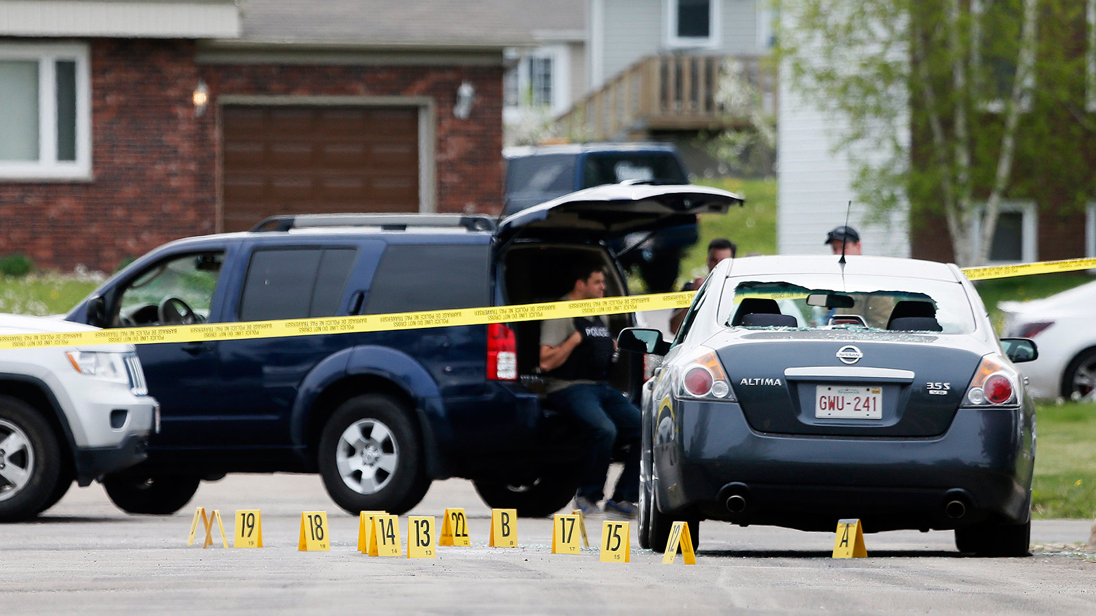Evidence markers lie on a street at the scene of a shooting incident in the eastern city of Moncton, New Brunswick June 5, 2014. Canadian police mounted the massive hunt on Thursday for a 24-year-old man, Justin Bourque, armed with high-powered weapons who they suspect shot dead three police officers and wounded two more in Moncton. Christinne Muschi/Reuters