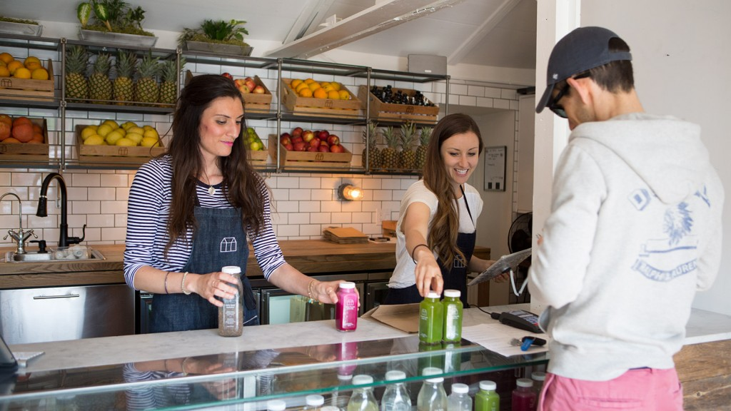 Staff at Greenhouse Juice Co. in Toronto help a customer purchase raw organic cold-pressed juice.
