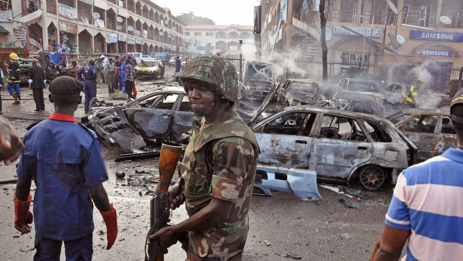 A Nigerian soldier,  center, walks, at the scene of an explosion in Abuja, Nigeria on Wednesday, June 25, 2014. (Olamikan Gbemiga/AP)