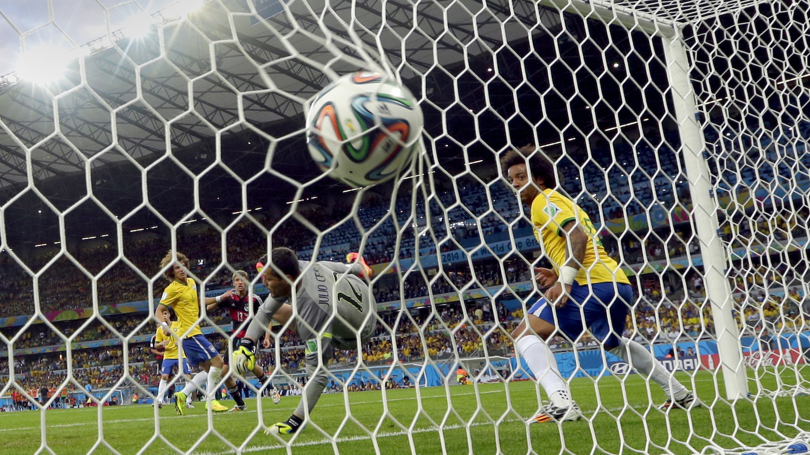 Brazil's goalkeeper Julio Cesar can not stop a shot by Germany's Thomas Mueller, background, to score his side's first goal during the World Cup semifinal soccer match between Brazil and Germany at the Mineirao Stadium in Belo Horizonte, Brazil, Tuesday, July 8, 2014. (AP Photo/Andre Penner)