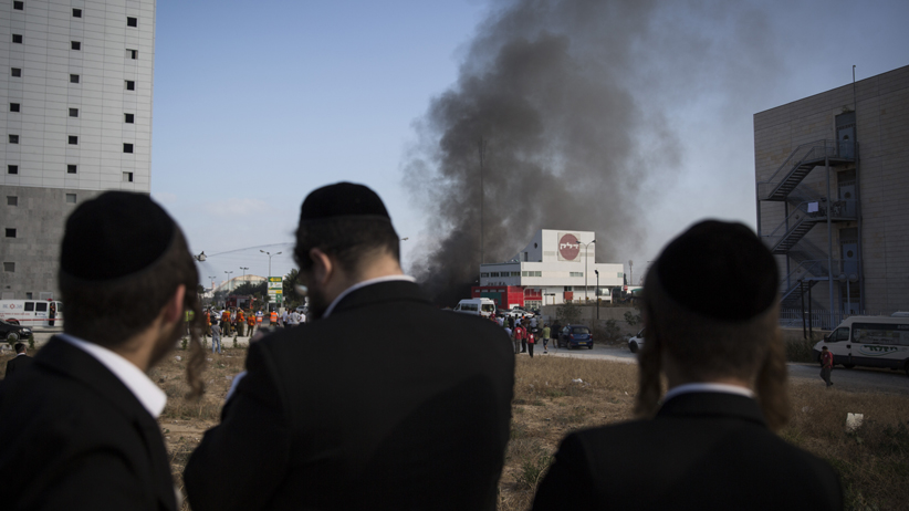 Ultra Orthodox Jews watch the smoke rising from a gas station in Ashdod