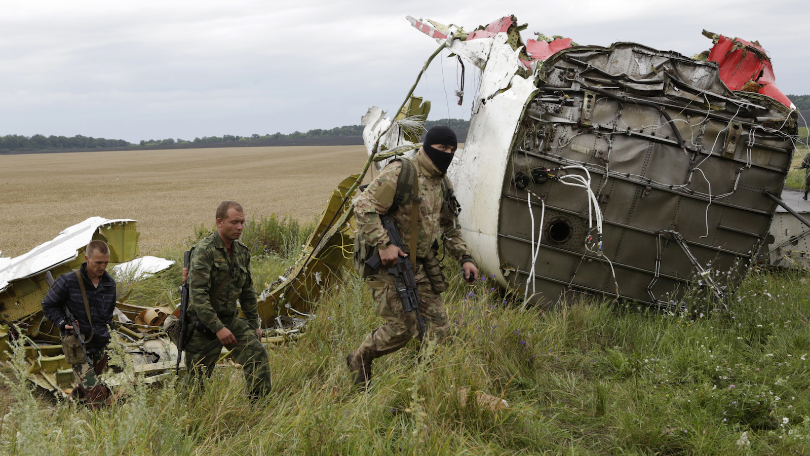 Pro-Russian fighters walk at the site of a crashed Malaysia Airlines passenger plane near the village of Hrabove, Ukraine, eastern Ukraine Friday, July 18, 2014. Rescue workers, policemen and even off-duty coal miners were combing a sprawling area in eastern Ukraine near the Russian border where the Malaysian plane ended up in burning pieces Thursday, killing all aboard. (AP Photo/Dmitry Lovetsky)