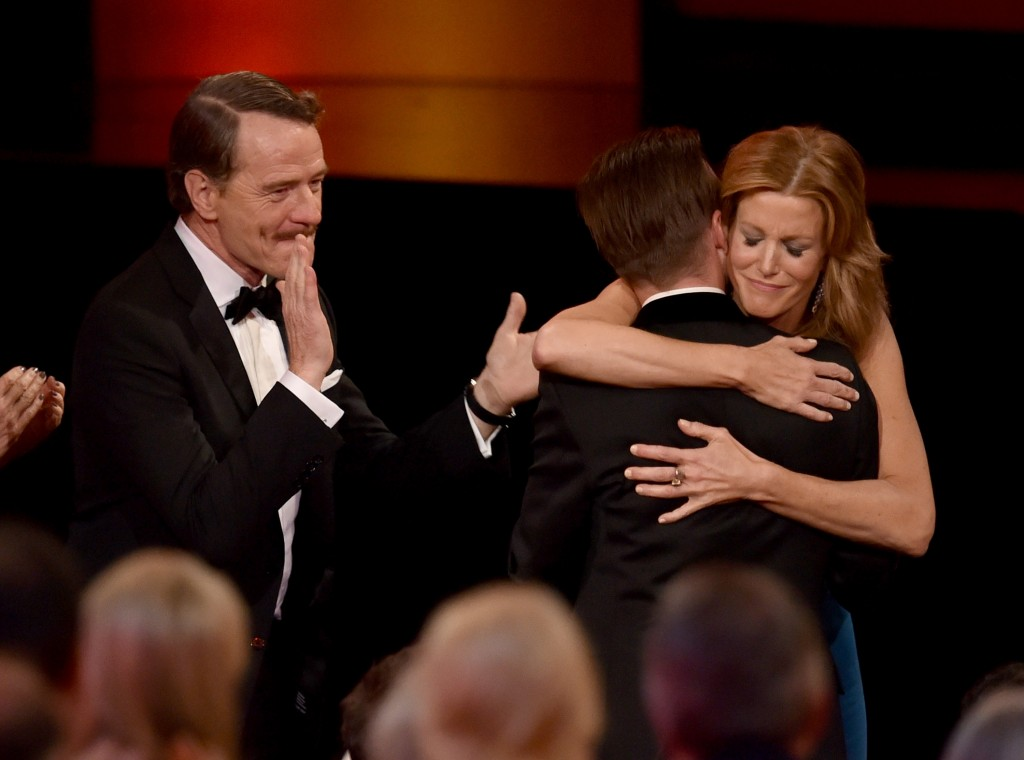 Bryan Cranston claps as Anna Gunn (right) hugs Aaron Paul in the wake of Breaking Bad's Emmy win for best drama.