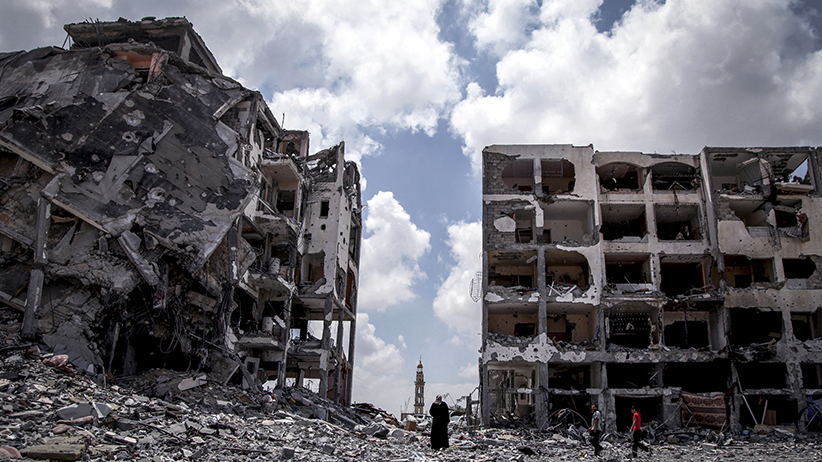 Palestinians walk in front of buildings destroyed by Israeli military forces in the northern Gaza Strip town of Beit Lahiya. Emad Nasser/Flash90/Redux