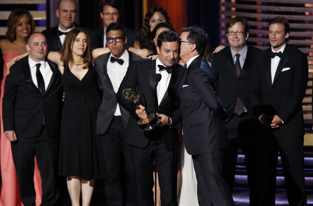 "Stephen Colbert whispers to Jimmy Fallon as he helps Colbert accept the award for Outstanding Variety Series for Comedy Central's ""The Colbert Report"" onstage during the 66th Primetime Emmy Awards. (Mario Anzuoni/Reuters)"