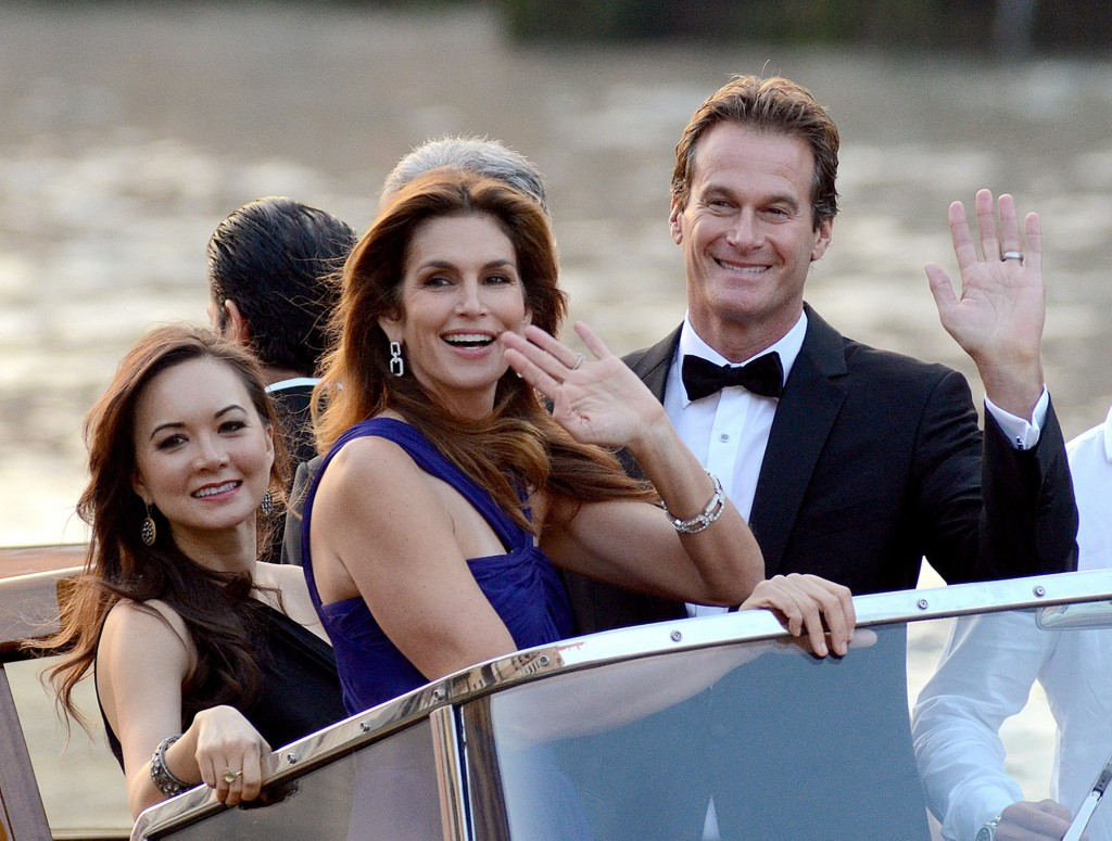 Cindy Crawford and Rande Gerber wave from a boat as they go to George Clooney's wedding. (AP Photo)