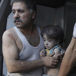 A man holds a child that survived from under rubble, after what activists claim was five air strikes by forces loyal to Syria's President Bashar al-Assad in Douma