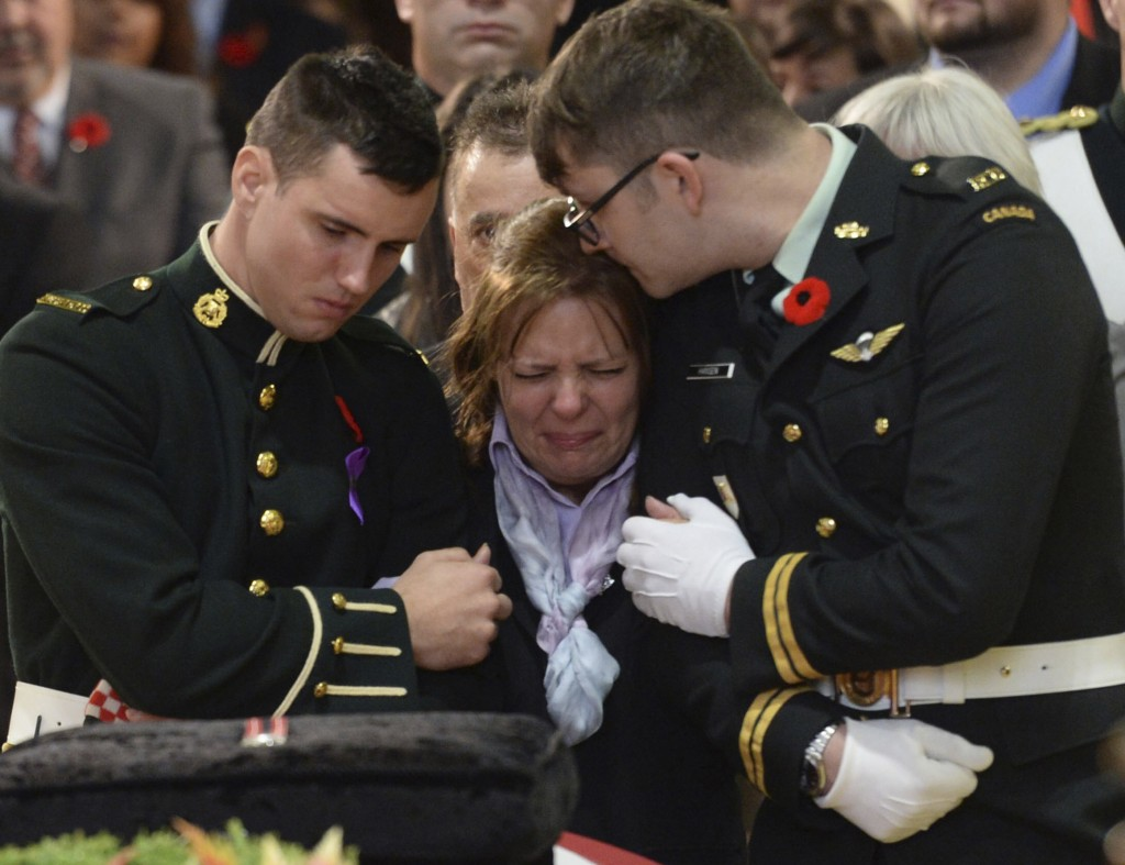 Kathy Cirillo is comforted in front of the coffin of her son Cpl. Nathan Cirillo at his regimental funeral service in Hamilton, Ontario. (Nathan Denette/CP)