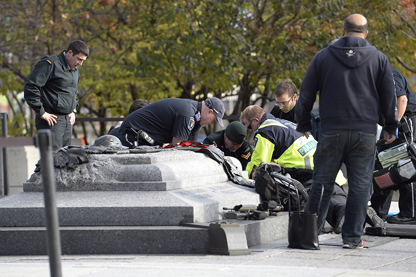 A soldier, police and paramedics tend to a soldier shot at the National Memorial near Parliament Hill in Ottawa on Wednesday Oct.22, 2014. (Adrian Wyld/The Canadian Press)