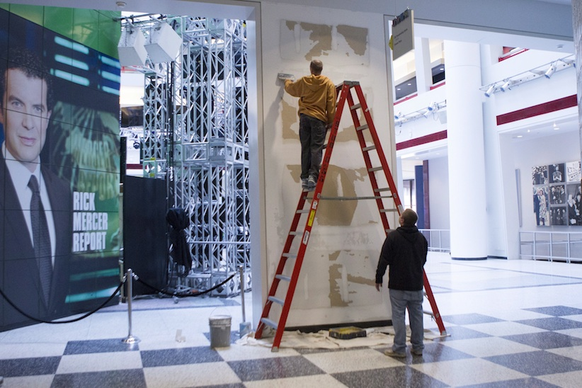 Workers scrape a wall which had a publicity photo of former CBC radio host Jian Ghomeshi in the broadcasting corporation's Toronto offices on Monday October 27, 2014. (Chris Young, The Canadian Press)
