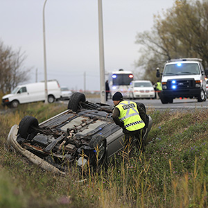 Surete du Quebec officer investigates an overturned vehicle in Saint-Jean-sur-Richelieu