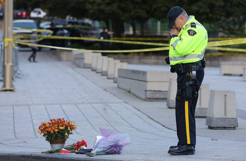 A RCMP officer looks at floral tributes to Cpl. Nathan Cirillo. Police continue to investigate in the aftermath of a shooting in Ottawa, where a soldier murdered at the War Memorial and a gun battle in Parliament killed the alleged gun man. in Ottawa. October 23, 2014.  (Steve Russell/Toronto Star)