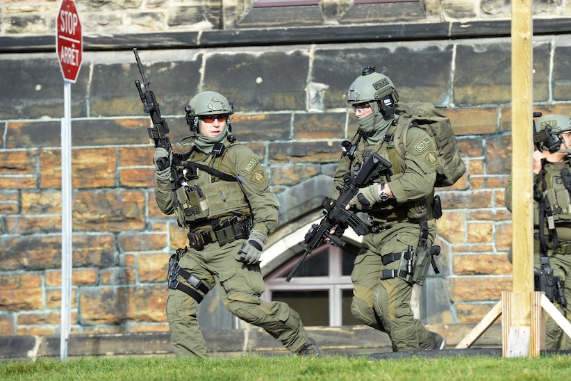 An RCMP intervention team run next to a Parliament building in Ottawa Wednesday. A Canadian soldier standing guard at the National War Memorial in Ottawa has been shot by an unknown gunman and there are reports of gunfire inside the halls of Parliament. Adrian Wyld/CP