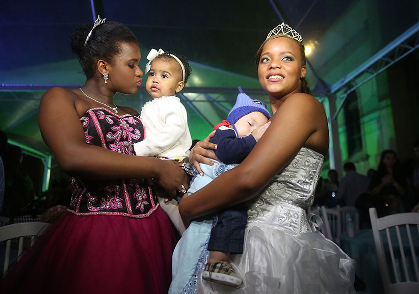 Debutantes: Teens from Rio de Janeiro's favelas pose with their children before attending a ball meant to create goodwill between residents and police. Mario Tama/Getty Images
