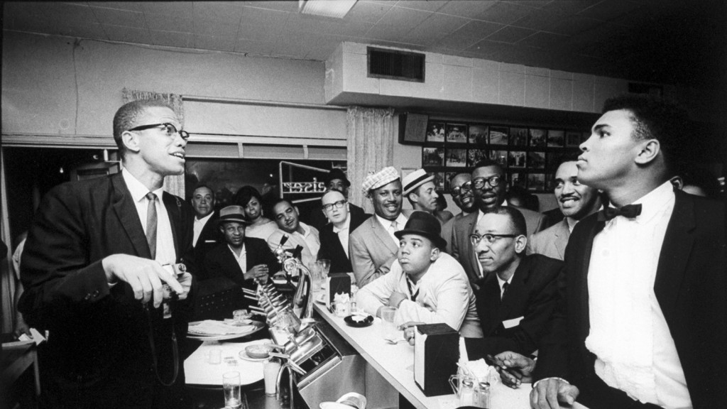 Black Muslim leader Malcolm X, left, behind soda fountain, joking with tux-clad Muhammad Ali, who responds with mock indignation while surrounded by jubilant fans after he beat Sonny Liston for the heavyweight championship of the world. (Bob Gomel/Getty Images)