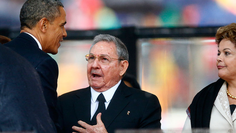 U.S. President Barack Obama (L) greets Cuban President Raul Castro (C) before giving his speech, as Brazil's President Dilma Rousseff looks on, at the memorial service for late South African President Nelson Mandela at the First National Bank soccer stadium, also known Soccer City, in Johannesburg December 10, 2013. (Kai Pfaffenbach, Reuters)