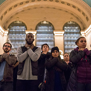 Protesters observe a moment of silence in a chokehold gesture during a march at Grand Central Station for Eric Garner in New York