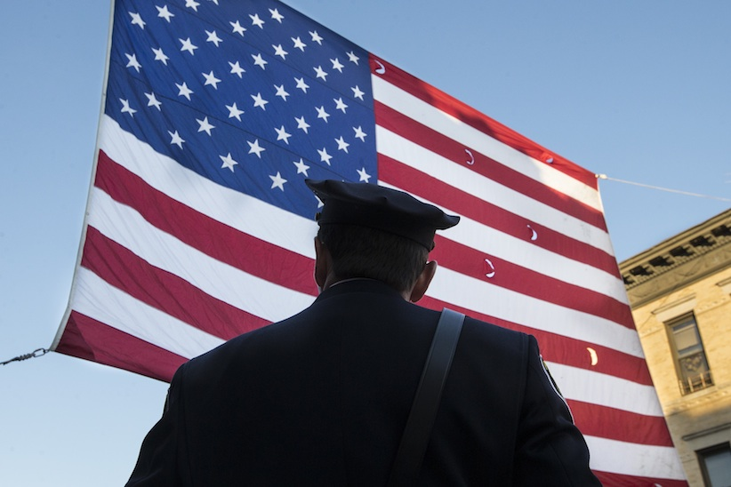 A police officer waits for the funeral of New York City police officer Rafael Ramos in the Glendale section of Queens, Saturday, Dec. 27, 2014, in New York. Ramos and his partner, officer Wenjian Liu, were killed Dec. 20 as they sat in their patrol car on a Brooklyn street. The shooter, Ismaaiyl Brinsley, later killed himself. (John Minchillo, AP Photo)