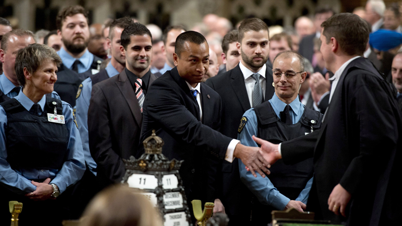 House of Commons Speaker Andrew Scheer shakes hands with Const. Samearn Son as other security members look on in the House of Commons as they are honoured for their efforts during the October shooting on Parliament Hill, Thursday December 11, 2014 in Ottawa. (Adrian Wyld/CP)