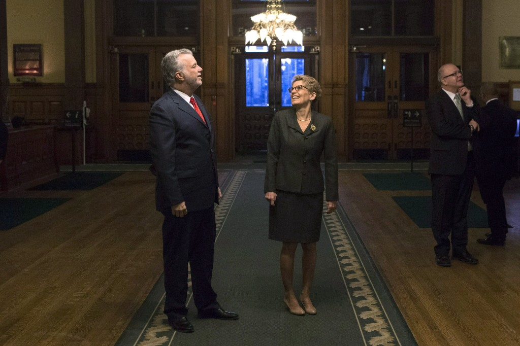 Ontario Premier Kathleen Wynne (centre) shows Quebec Premier Philippe Couillard (left) artwork in the hallway at the Ontario Legislature in November, 2014. (Chris Young/The Canadian Press)