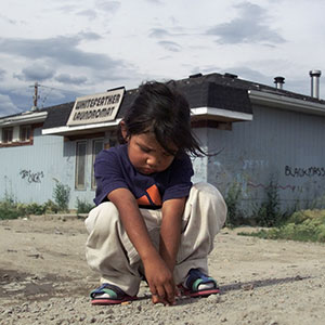 Pikangikum_SadGirl50-07/24/01-A sad young girl plays by herself on a dusty road in Pikangikum. Pikan