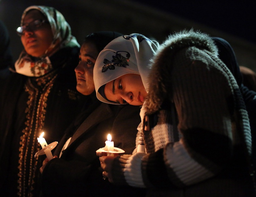 Suzanne Askar, right, rests her head on the shoulder of Safam Mahate, a student at North Carolina State University, as they stand next to Nida Allam, far left, during a vigil for three people who were killed at a condominium near UNC-Chapel Hill on Wednesday. (AP Photo)