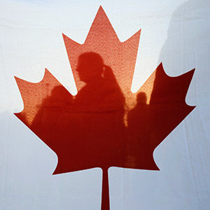 Israelis are silhouetted behind a Canadian flag at a rally to thank Canada's PM Harper for his support of Israel during his visit at the Israeli parliament in Jerusalem