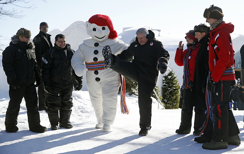 Canada's Prime Minister Stephen Harper kicks next to a Bonhomme Carnaval mascot at the Ice Hotel in Quebec City
