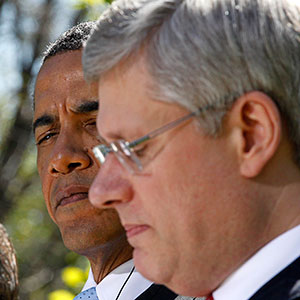 U.S. President Obama listens to Canada's Prime Minister Harper during joint news conference with Mexico's President Felipe Caldero Mexico's President Calderon in the White House Rose Garden in Washington