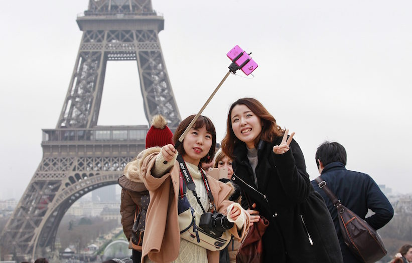 Tourists use a selfie stick on the Trocadero Square, with the Eiffel Tower in background, in Paris, Tuesday, Jan. 6, 2015. (Remy de la Mauviniere/AP Photo)