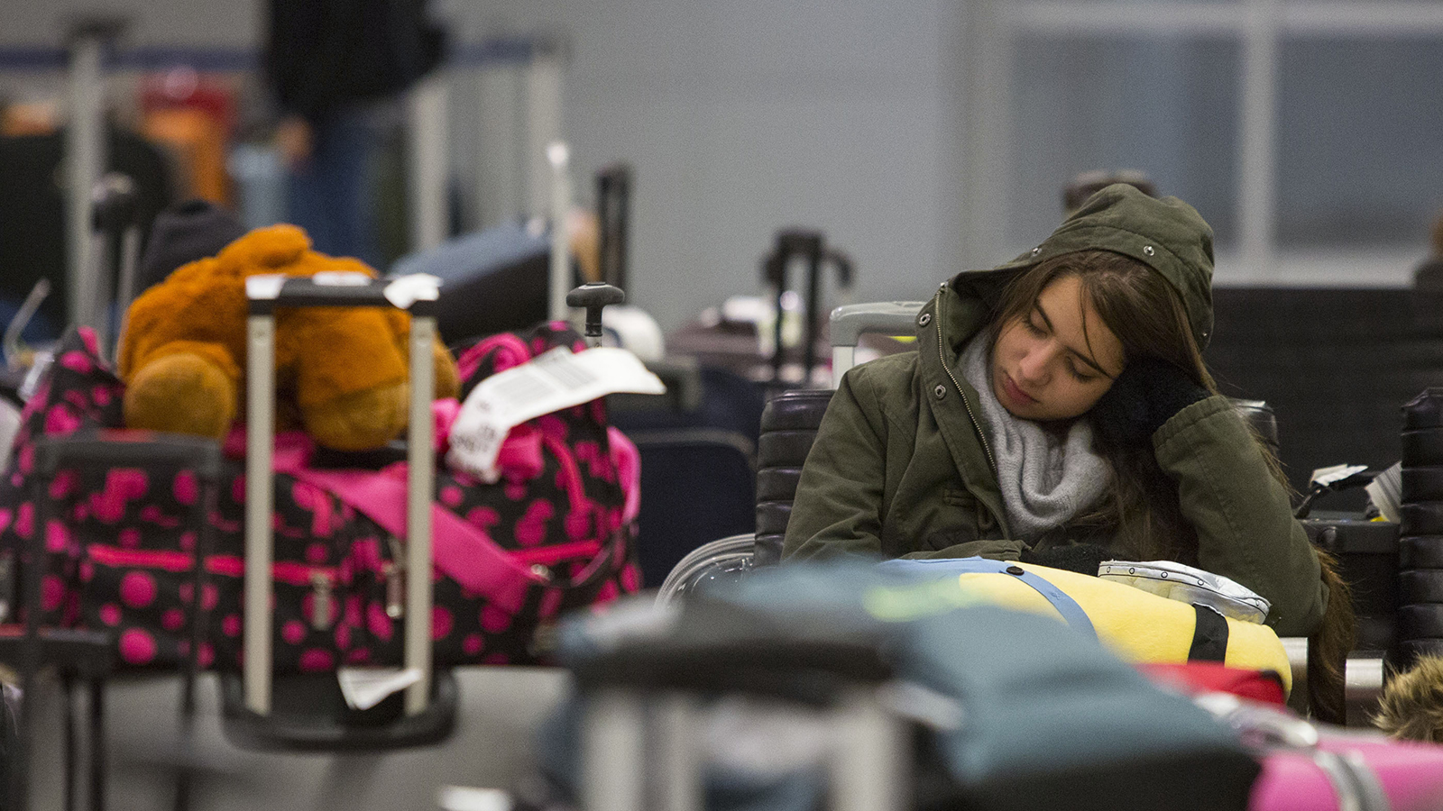 A woman tries to sleep amongst baggage at the John F. Kennedy International Airport in New York