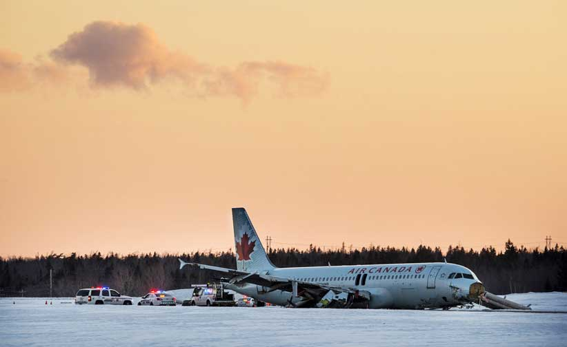 Crew members work on the Airbus A320 that slid off a runway at the end of Air Canada Flight 624 at Halifax Stanfield Airport in Enfield, Nova Scotia